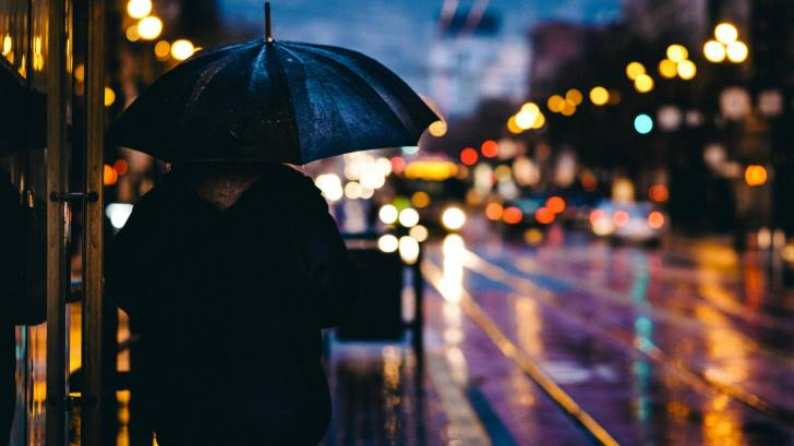 adult with an umbrellaon a rainy street with lights on it
