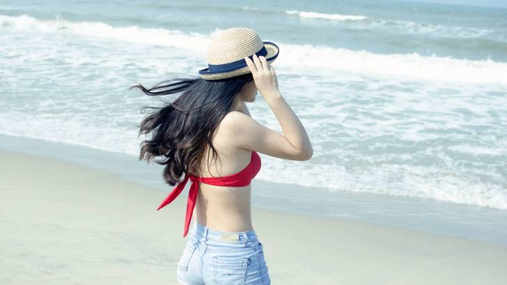 young girl on beach, fit, this with shorts and red top and hat