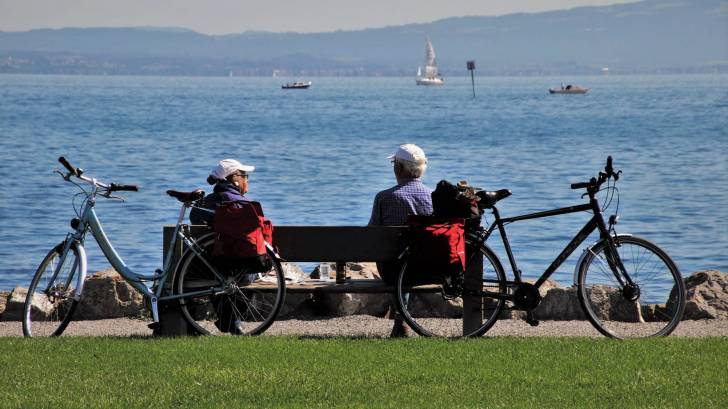 older couple on a bench with their bikes looking at a lake