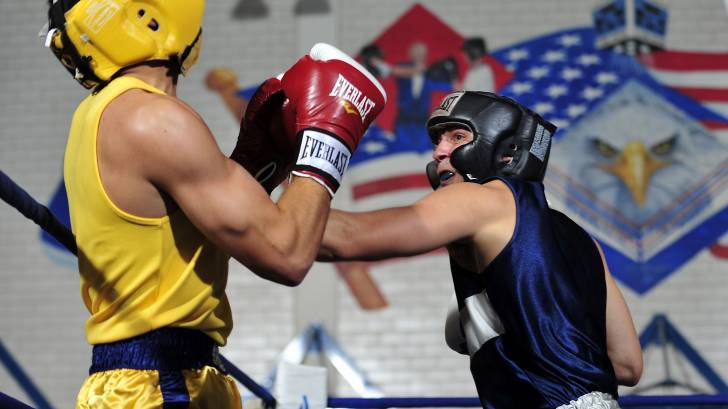 men boxing/fighting in a ring