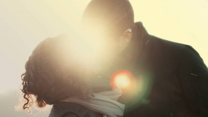 happy couple kissing in the sunlight