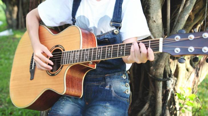 coed playing a guitar on campus