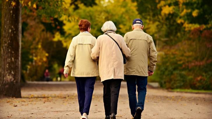 three older friends walking arm in arm