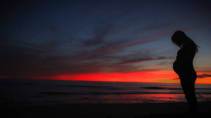 pregnant woman on beach at sun set