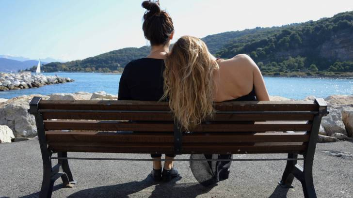 sisters on a bench overlooking the water, sharing a moment