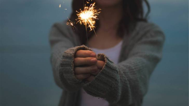 woman holding a sparkler celebrating