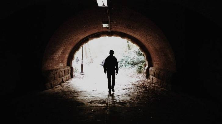 man walking in a tunnel heading towards the light, hopeful