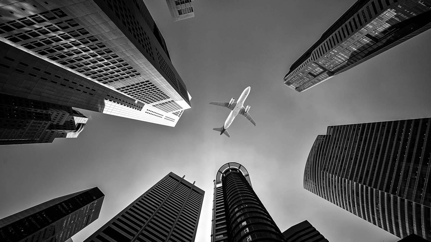 jet liner flying through the air in between buildings
