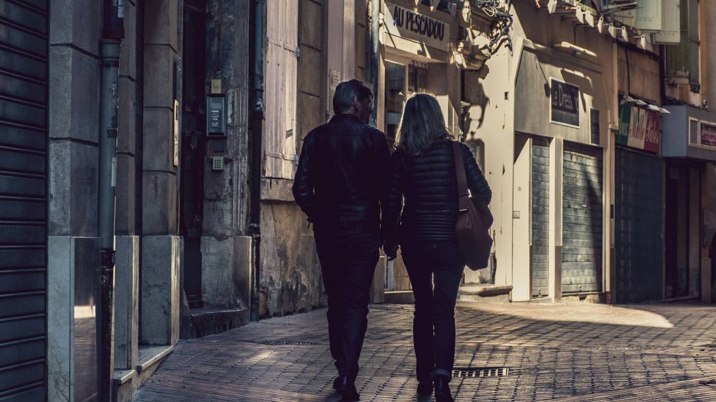 older couple walking thru an old town in europe