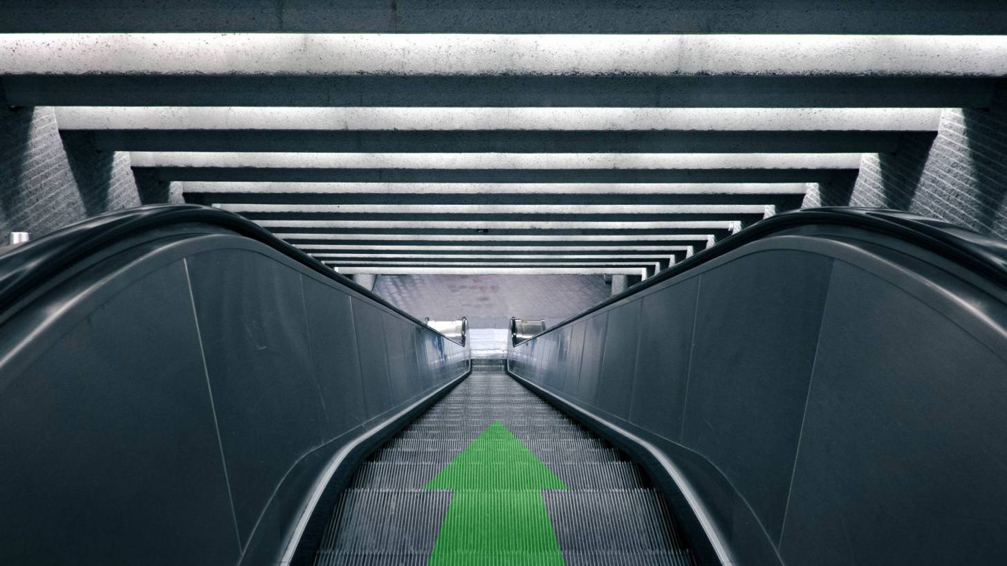 down escalator with green arrow indication down
