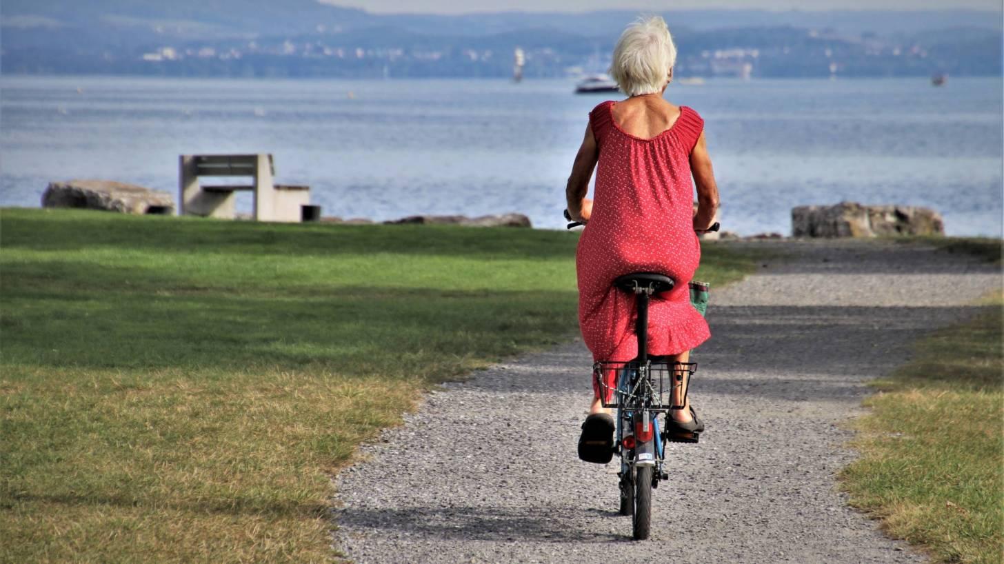 senior woman riding a bike near the ocean