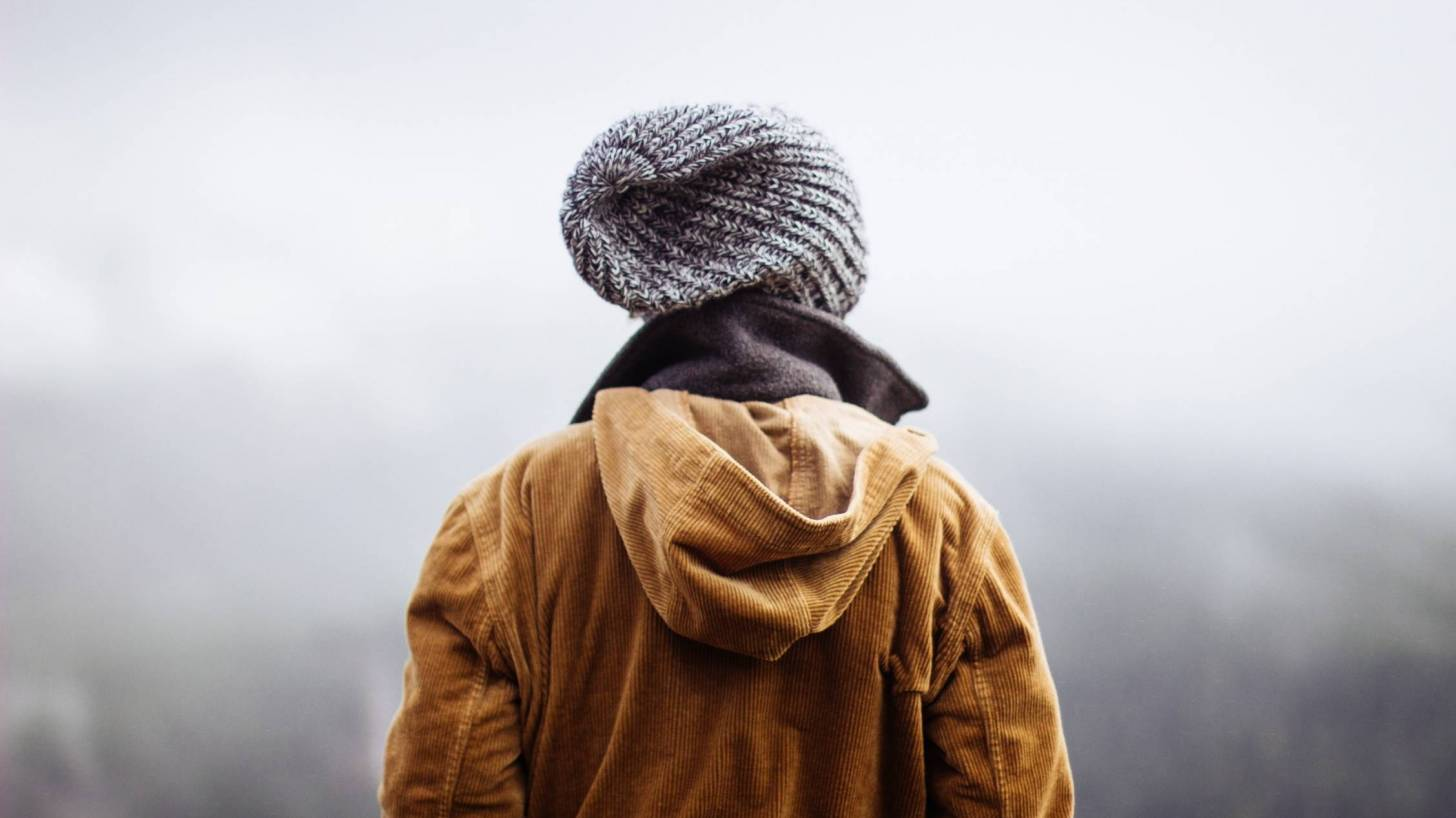 man looking forlornly into the foggy mist