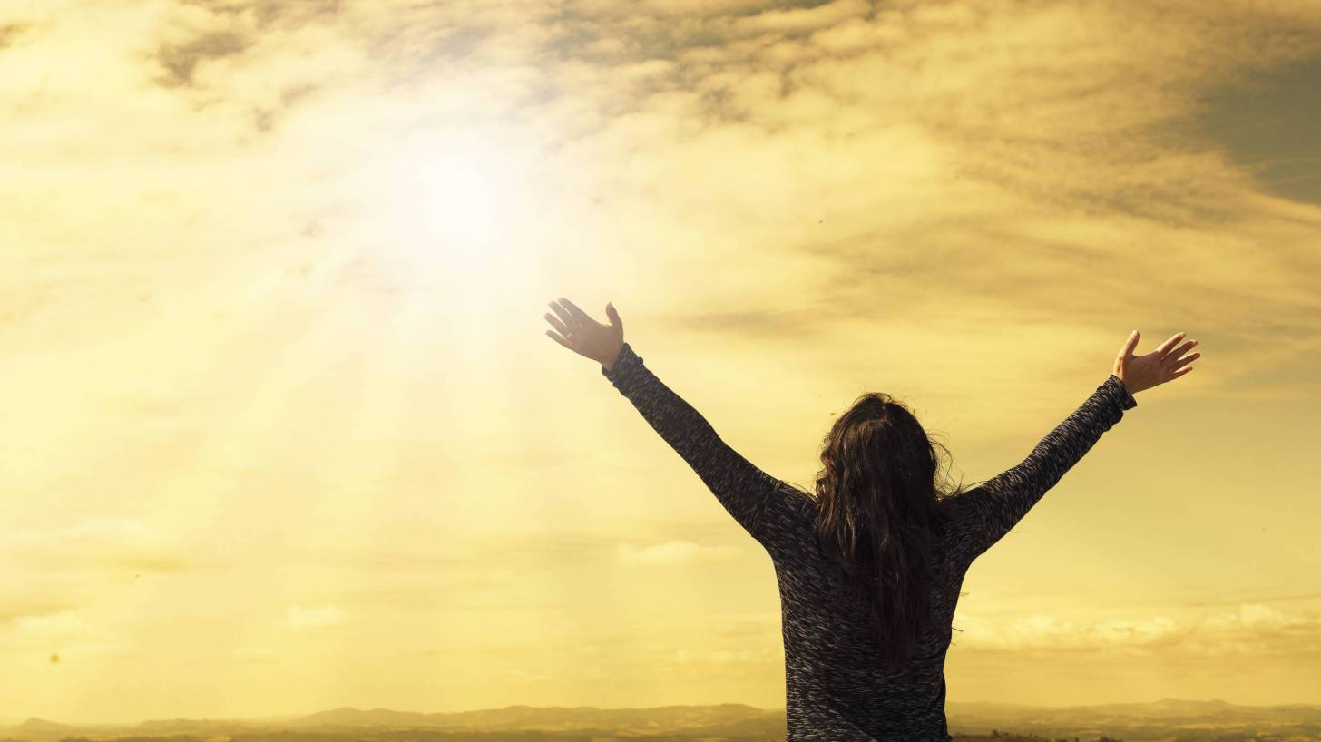 hopeful woman praising the sky