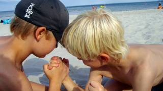 young boys arm wrestling on the beach