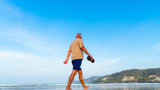 older man walking on a sunny beach