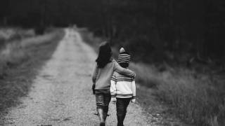 two young children walking down the road together