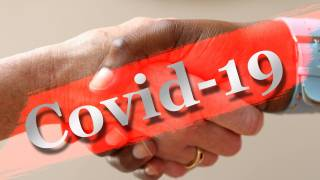 hand shking with COVID-19 written on top