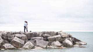 young couple kissing on a rock jetty
