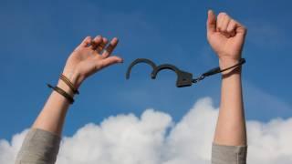man breaking free of hand cuffs, addiction