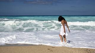 young woman walking on a sandy beach in the surf