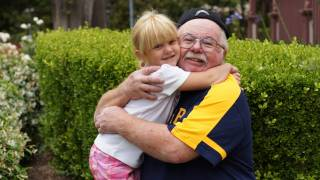 happy healthy grandpa hugging his grand daughter