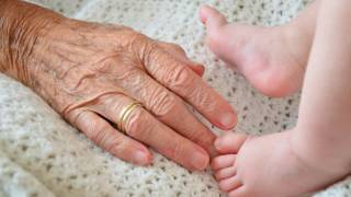 grandma's hand in crib with baby feet, generations