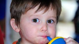 young boy drinking from a sippy cup