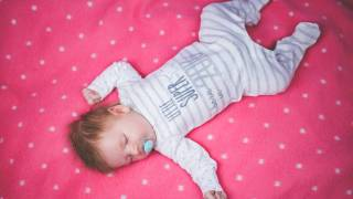 cute infant sleeping on a blanket happy with paci in mouth