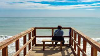 old man sitting on bench looking at the sea