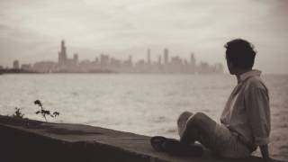 man sitting on a sea wall looking back at the city