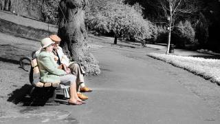 older couple sitting on a park bench