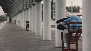 homeless person sleeping under a bridge