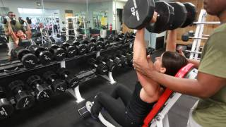 woman with a trainor lifting weights