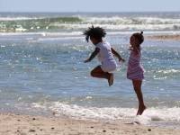 children jumping high in the ocean