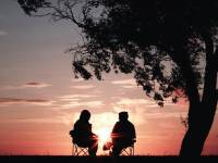 older people sitting watching the sunset