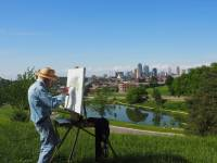 older man painting a scene on a sunny day