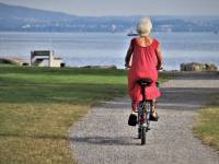 senior woman riding a bike near the ocean