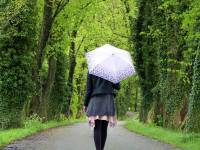 young women with an umbrella wlaking down a tree lined path